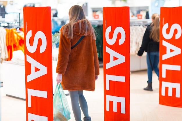 Jeune femme passe par un cadre antivol de sécurité dans un magasin