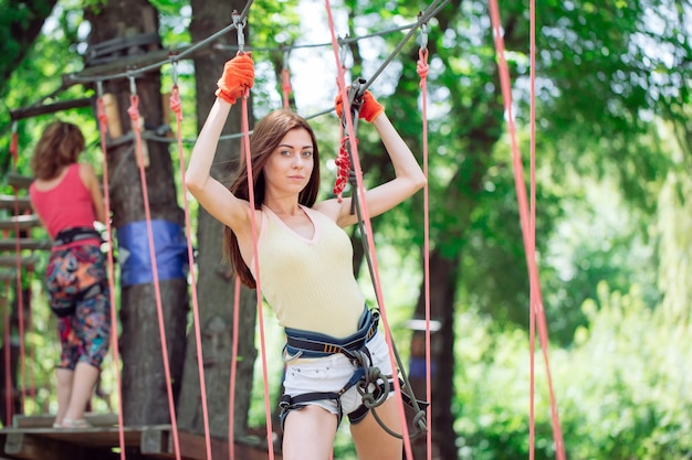 Jeune femme passe ses loisirs dans un parcours de cordes. femme engagée dans le parc de corde.