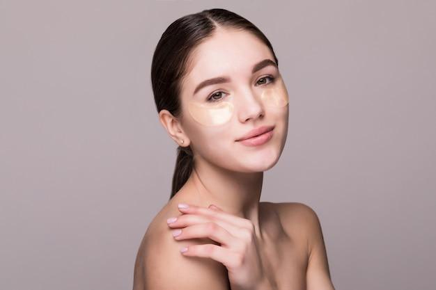 Jeune femme avec un patch oculaire touchant les temples isolés sur un mur gris. cosmétiques, concept de stress cutané