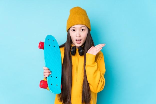Jeune femme de patineur chinois isolée surprise et choquée.