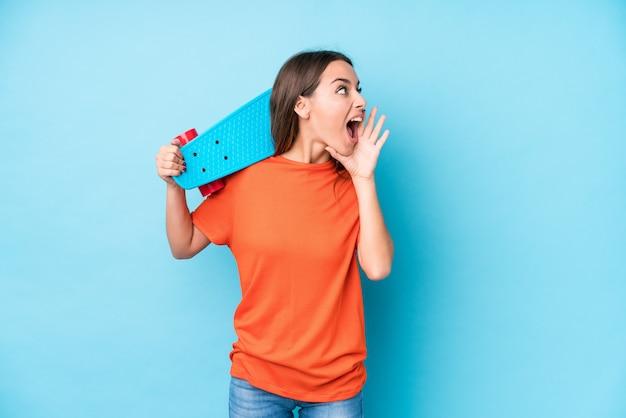 Jeune femme patineuse caucasienne isolée criant et tenant la paume près de la bouche ouverte.