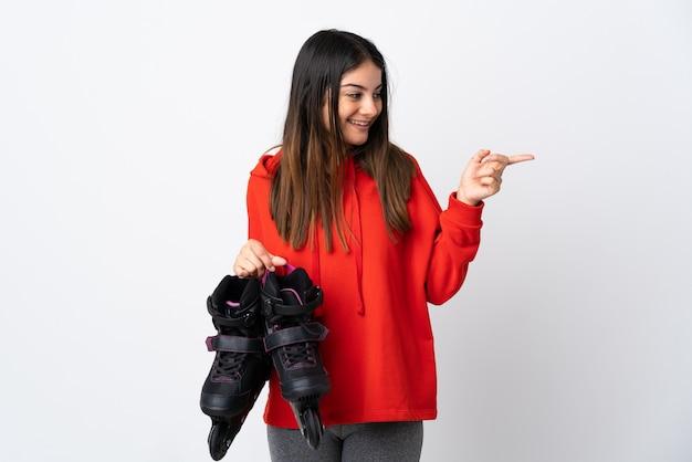 Jeune femme patineuse isolée sur blanc doigt pointé sur le côté et présentant un produit