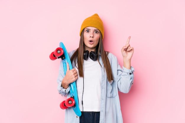 Jeune femme patineuse tenant un patin ayant une excellente idée, concept de créativité.