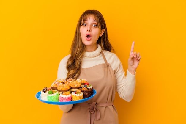 Jeune femme pâtissière isolée sur fond jaune ayant une bonne idée, concept de créativité.