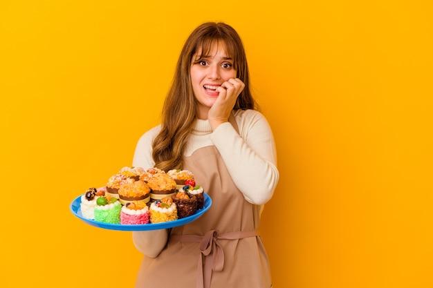 Jeune femme pâtissière isolée sur fond jaune se rongeant les ongles, nerveuse et très anxieuse.