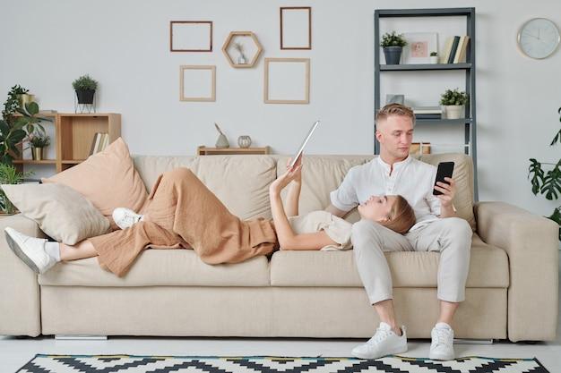 Jeune femme avec pavé tactile gardant la tête sur les genoux de son mari utilisant un smartphone en position allongée sur un canapé et en faisant défiler les pages en ligne