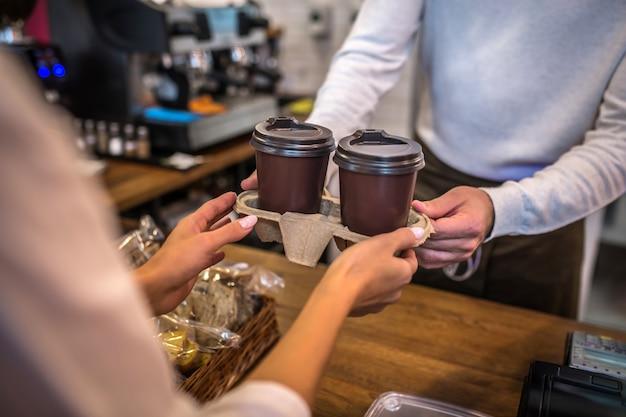 Jeune femme payant dans un café