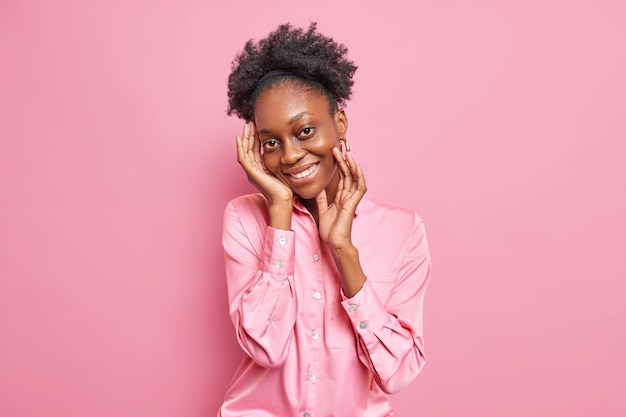 Une jeune femme à la peau assez foncée avec des cheveux bouclés et peignés touche le visage sourit doucement à pleines dents a l'expression du visage satisfait