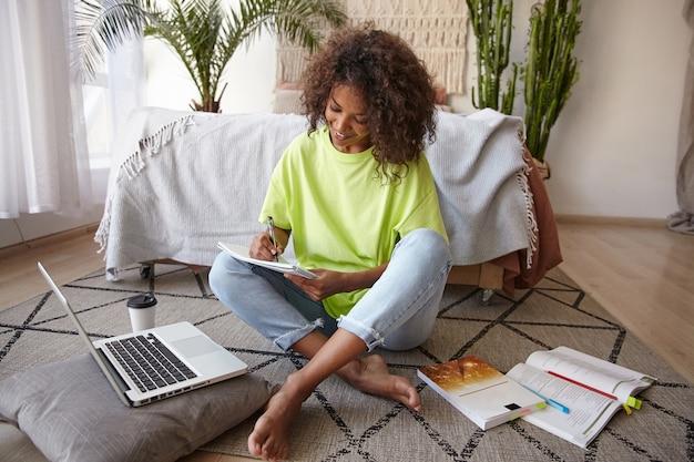 Jeune femme à la peau foncée aux cheveux bouclés bruns étudiant dans la chambre à coucher, prenant des notes avec un visage heureux, portant des jeans et un t-shirt jaune