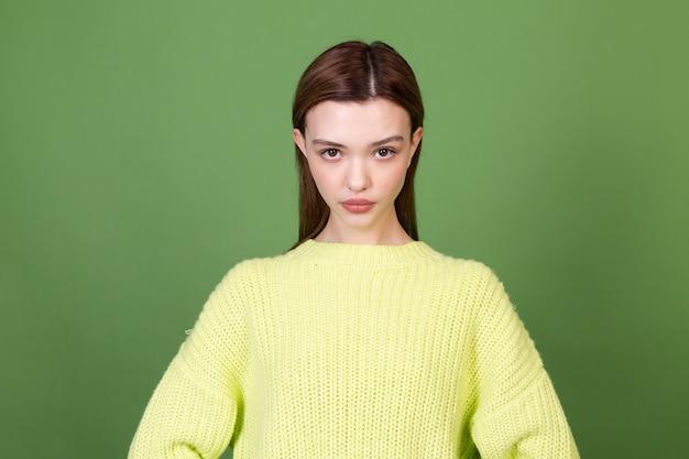 Jeune femme avec une peau naturelle propre et parfaite et de grandes lèvres brunes maquillées sur un mur vert posant