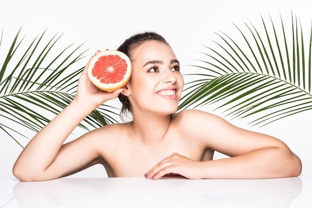 Jeune femme avec une peau parfaite tenant des agrumes à la main entourée de feuilles de palmiers isolé sur mur blanc