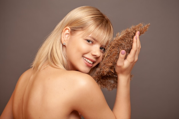 Jeune femme avec une peau saine et fraîche et des cheveux tenant des fleurs séchées et souriant.