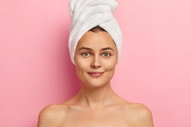 Jeune femme à la peau saine et lisse, a le corps nu, regarde droit devant, a les yeux bleus, porte une serviette sur la tête, prend une douche dans la salle de bain