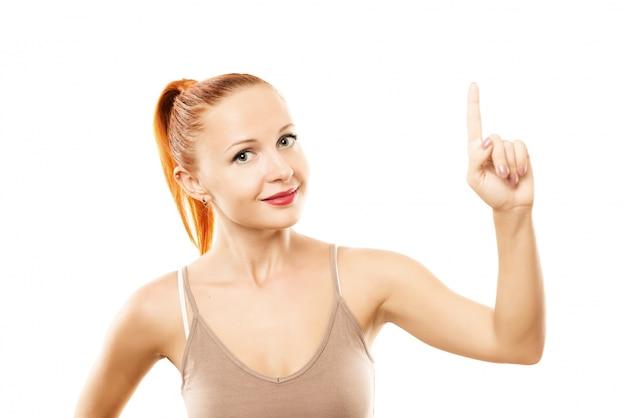 Jeune femme avec une peau saine pointant vers le haut