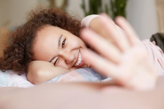 Jeune femme à la peau sombre en riant allongée sur le lit, profitez de la journée ensoleillée à la maison, souriant largement et a l'air heureux.