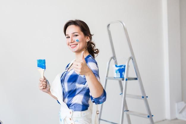 Jeune femme peignant le mur et a l'air très heureuse, elle montre le pouce vers le haut