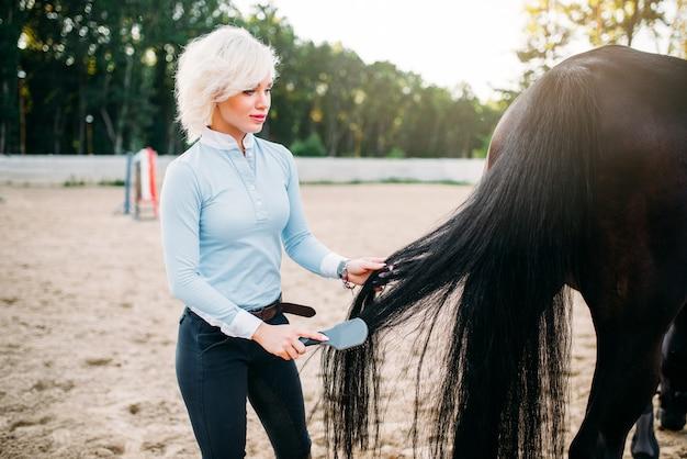 Jeune femme peignant la queue du cheval.