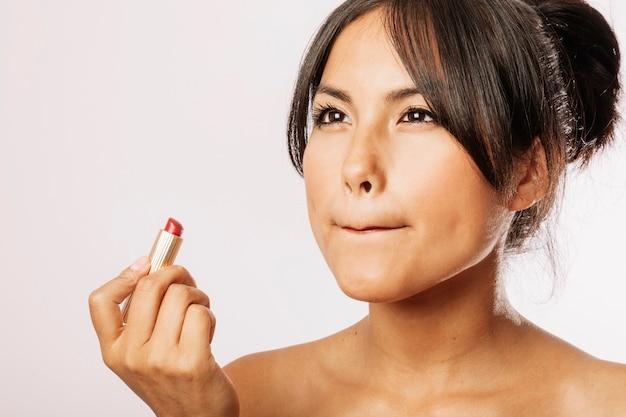 Jeune femme peignant ses lèvres