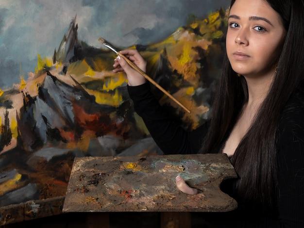 Jeune femme peignant une toile sur un chevalet.