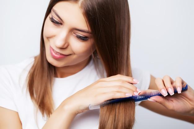 Jeune femme peigne ses beaux cheveux avec un peigne