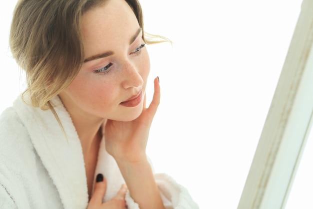 Jeune femme avec peignoir après la douche