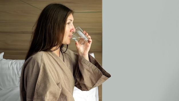Jeune femme en peignoir beige boit de l'eau propre assise dans une chambre d'hôtel en gros plan tôt le matin
