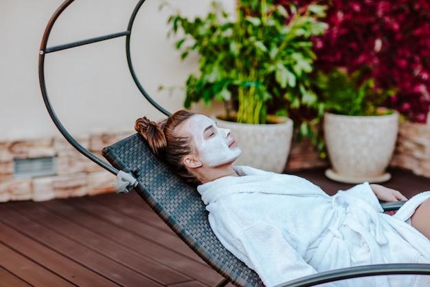 Jeune femme en peignoir blanc et masque sur son visage
