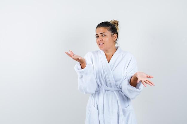 Jeune femme en peignoir blanc s'étendant les mains de manière interrogative et à la perplexité