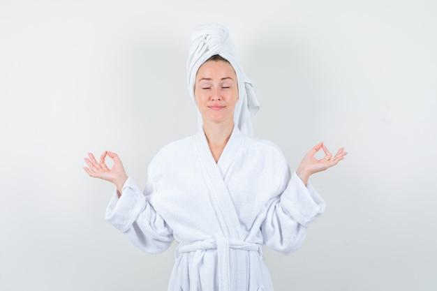 Jeune femme en peignoir blanc, serviette montrant le geste de méditation et à la vue détendue, de face.