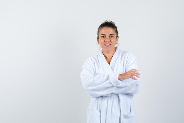 Jeune femme en peignoir debout avec les bras croisés et à la confiance