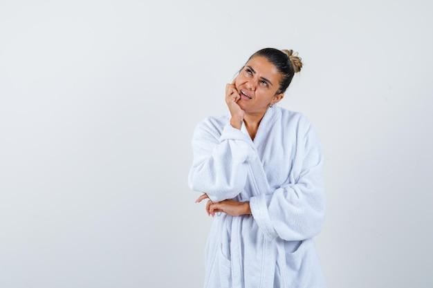 Jeune femme en peignoir debout dans une pose de réflexion et à la réflexion