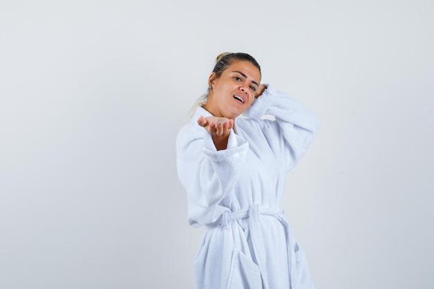 Jeune femme en peignoir faisant semblant de montrer quelque chose et ayant l'air confiant