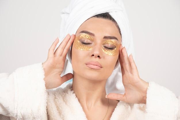 Jeune femme en peignoir et patchs cosmétiques pour les yeux posant.