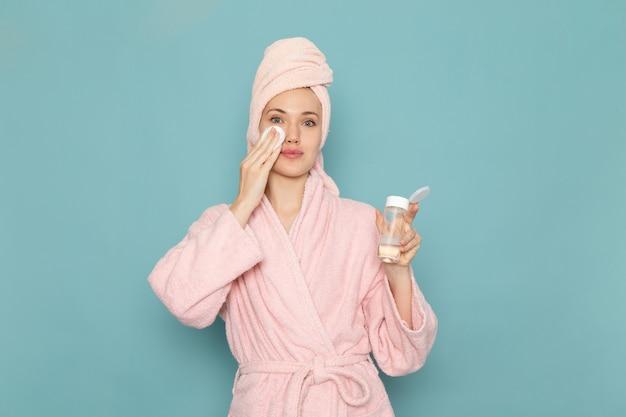 Jeune femme en peignoir rose après la douche à l'aide de nettoyant maquillage sur bleu