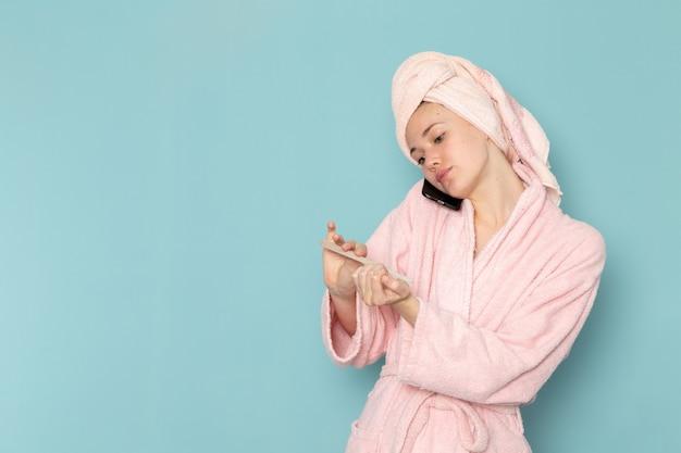 Jeune femme en peignoir rose après la douche fixant ses ongles sur bleu