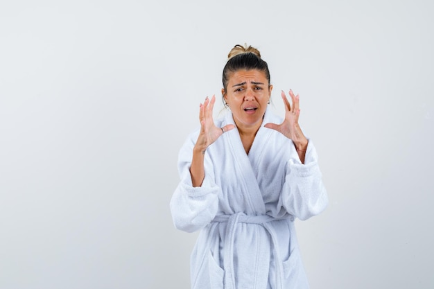 Jeune femme en peignoir s'étendant la main dans un geste de questionnement et à la confusion