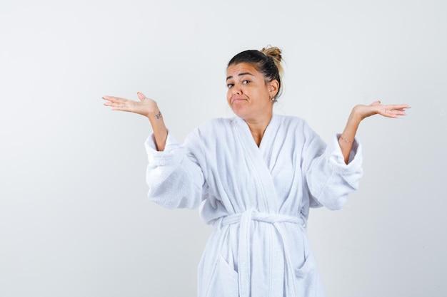 Jeune femme en peignoir s'étendant les mains de manière interrogative