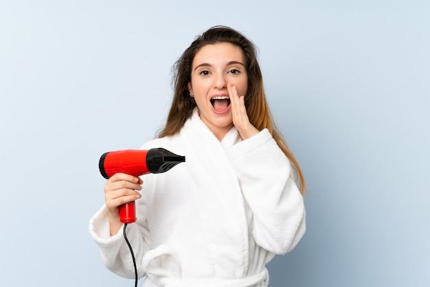 Jeune femme en peignoir avec sèche-cheveux criant avec la bouche grande ouverte