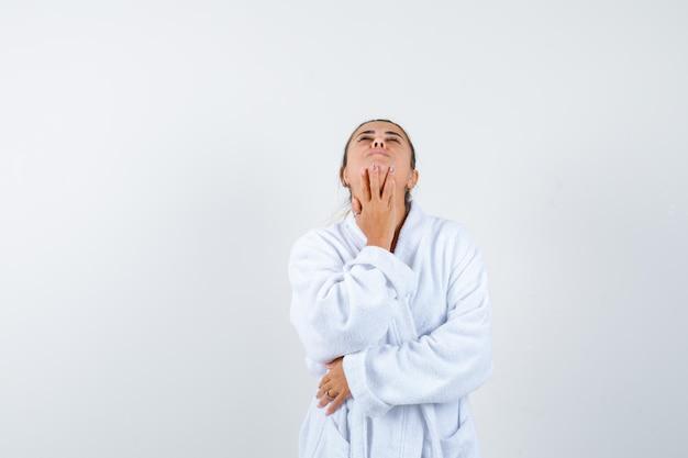 Jeune femme en peignoir tenant les doigts sous le menton tout en levant les yeux et en regardant nostalgique