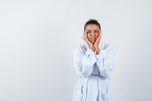 Jeune femme en peignoir tenant les mains sur les joues et à la mignonne