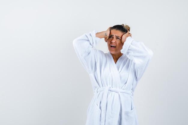 Jeune femme en peignoir tenant les mains sur la tête et l'air ennuyé