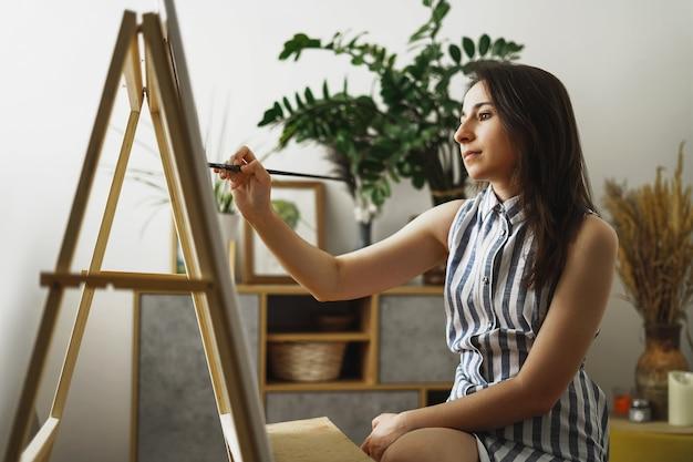 Une jeune femme peint dans son appartement avec des peintures à l'huile. une étudiante dessine dans un studio d'art. concept d'étude des beaux-arts.