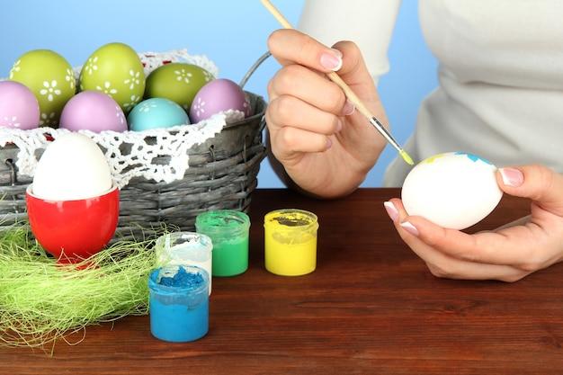 Jeune femme peinture des oeufs de pâques, sur la couleur
