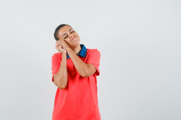 Jeune femme penchée joue sur les mains, essayant de dormir en t-shirt rouge et à la somnolence. vue de face.