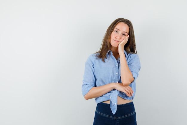 Jeune femme penchée joue sur la paume surélevée en chemise bleue, pantalon et à la pensif.