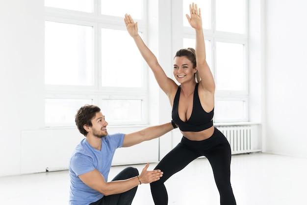 Jeune femme pendant l'entraînement avec un instructeur de fitness personnel dans la salle de gym. exercices de squats pour les fessiers et les hanches.