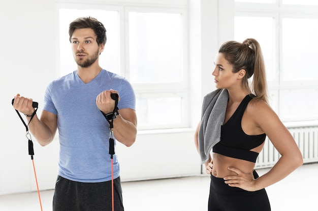 Jeune femme pendant l'entraînement avec un instructeur de fitness personnel utilisant des bandes de résistance en caoutchouc dans la salle de sport.