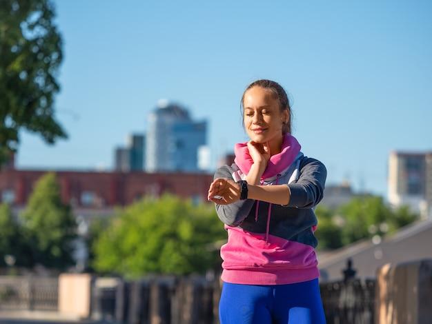 La jeune femme pendant le jogging matinal mesure le pouls en vérifiant les montres