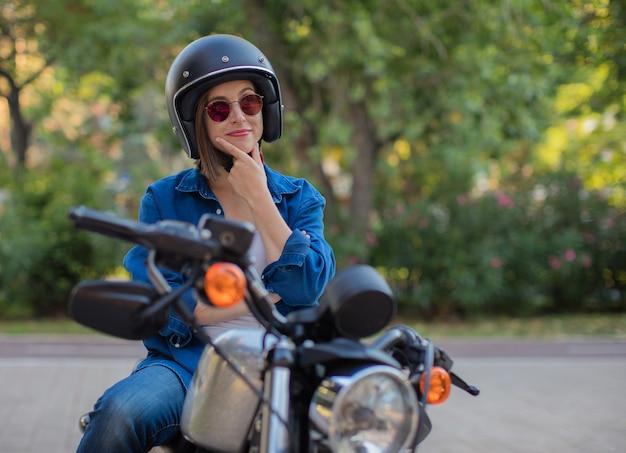 Jeune femme pensant sur une moto