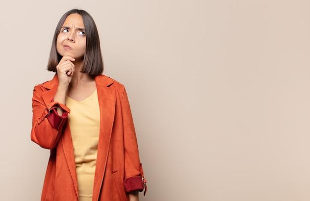Jeune femme pensant, se sentant dubitative et confuse, avec différentes options, se demandant quelle décision prendre